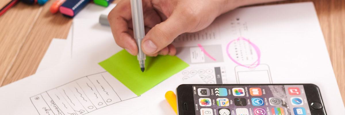 Mano abocentado la interfaz de una aplicación móvil en un post-it, es una parte del proceso de diseño