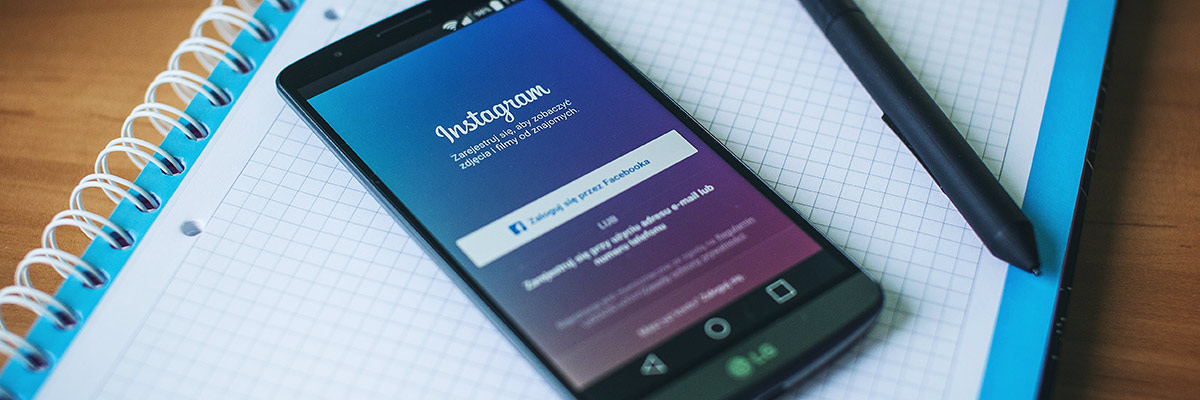 Dispositivo móvil junto con un cuaderno donde se ve el acceso a instagram perfil de empresa
