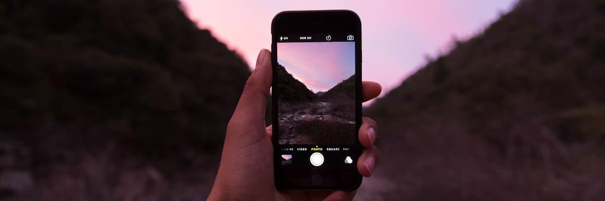 una mano sujeta un smartphone para realizar una fotografía de un paisaje